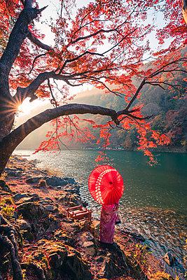 Arashiyama, Kyoto, Kyoto prefecture, Kansai region, Japan. Woman with red umbrella and kimono admiring the view on Katsura river (MR). - p651m2062120 by Marco Bottigelli