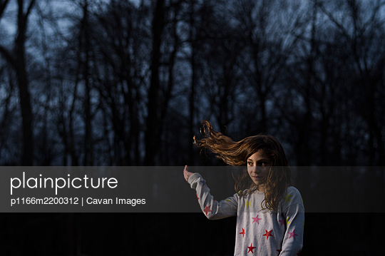 Girl flipping blonde hair at twilight - p1166m2200312 by Cavan Images