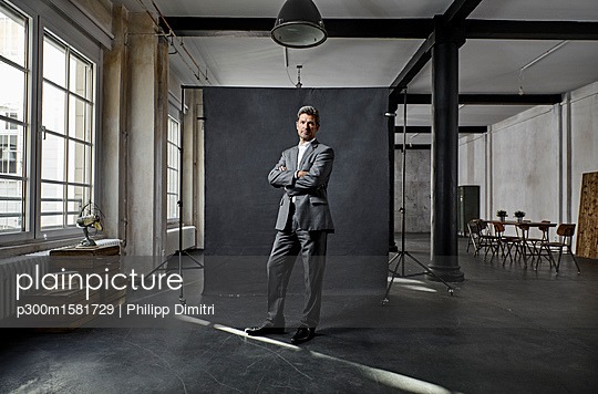 Portrait of mature businessman in front of black backdrop in loft - p300m1581729 von Philipp Dimitri