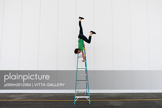 Acrobat balancing upside down on a ladder - p300m2012354 von VITTA GALLERY