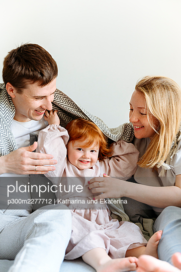 Playful girl sitting amidst parents under blanket on bed at home - p300m2277712 by Katharina und Ekaterina