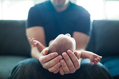 Midsection of father holding newborn baby while sitting at home - p1166m1474444 by Cavan Images