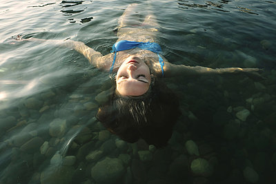 High angle view of carefree woman with eyes closed floating on water in river - p1166m1509537 by Cavan Images