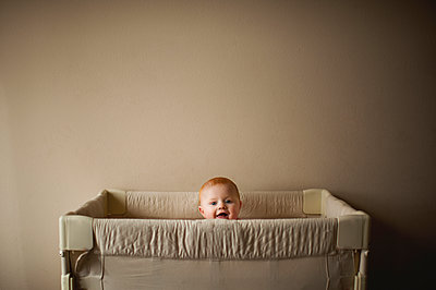 Portrait of baby boy in crib against wall at home - p1166m1512377 by Cavan Images