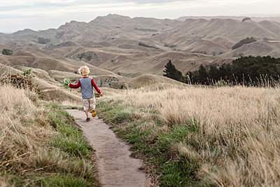 Young child running on a scenic path in New Zealand - p1166m2129483 by Cavan Images