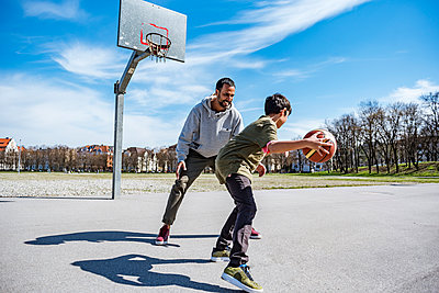 Father and son playing basketball on court outdoors - p300m1588050 von Daniel Ingold