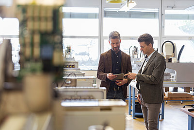 Two businessmen with tablet talking in factory - p300m1588106 by Daniel Ingold