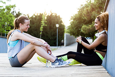 Two sporty young women relaxing on a bridge after workout - p300m2131998 by Josep Suria