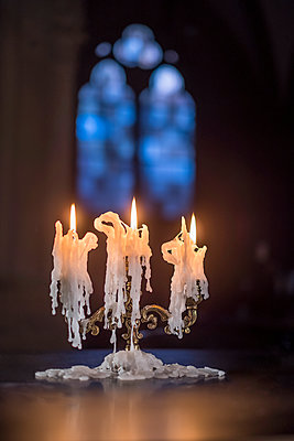 Lit candles against church window - p335m2177697 by Andreas Körner