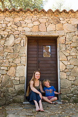 Mother and her son sit in front of stone house - p628m1476240 by Franco Cozzo