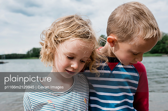 brother and sister cuddling each other whilst playing at the beach - p1166m2129945 by Cavan Images
