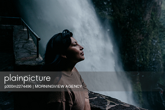 Woman contemplating while leaning on retaining wall by waterfall - p300m2274496 by MORNINGVIEW AGENCY