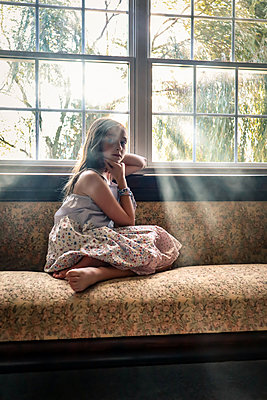 Young girl sits on sofa at the window - p1019m2134678 by Stephen Carroll