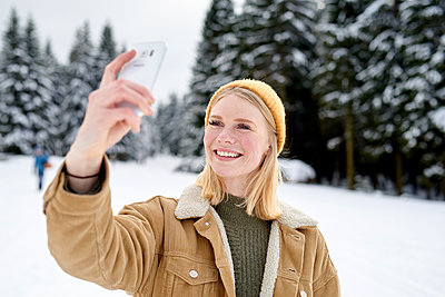 Young woman takes a selfie in the snow - p1124m1589306 by Willing-Holtz