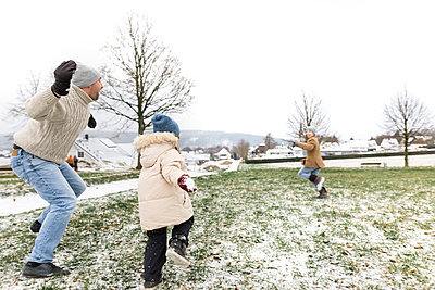 Father and two children having a snowball fight - p300m2080950 von Katharina Mikhrin
