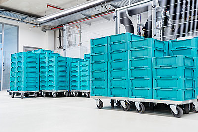 Turquoise colored containers inside modern factory warehouse, Stuttgart, Germany - p300m2131811 by Daniel Ingold