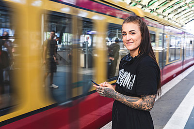 Portrait of tattooed young woman with smartphone and headphones standing on platform, Berlin, Germany - p300m2156863 von William Perugini