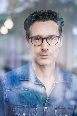 Mature businessman wearing spectacles  looking through office window - p429m1155589 by Philipp Nemenz