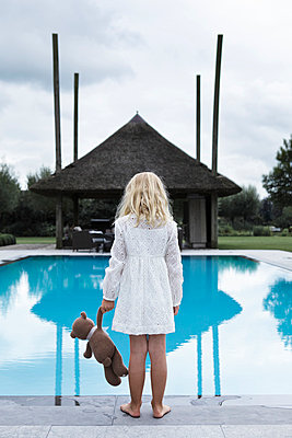 Little girl with teddy bear by swimming pool - p896m836163 by Rutger van der Bent