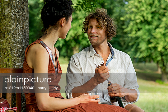 Paar beim Wein auf der runden Gartenbank - p1212m1159040 von harry + lidy