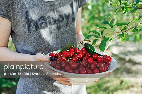 Teenager holding a plate with sweet cherries - p1412m1584258 by Svetlana Shemeleva