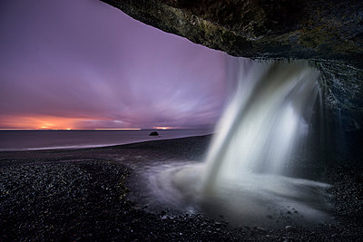 Idyllic view of waterfall at Mystic Beach against sky during dusk - p1166m1486054 by Cavan Images