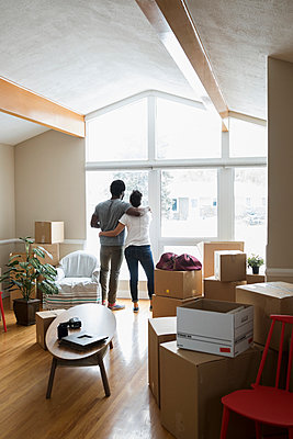 Affectionate couple at window moving into new home, surrounded by cardboard boxes - p1192m1559946 by Hero Images