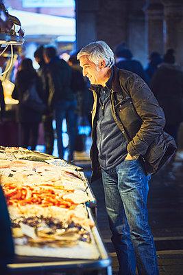 Mann begutachtet Meeresfrüchte an einem Fischstand in Venedig - p1312m2082206 von Axel Killian