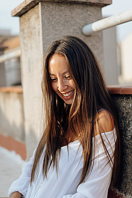 Portrait of laughing young woman relaxing on roof terrace - p300m2023521 von VITTA GALLERY