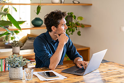 Male freelance worker contemplating while using laptop at table - p300m2276499 by Steve Brookland
