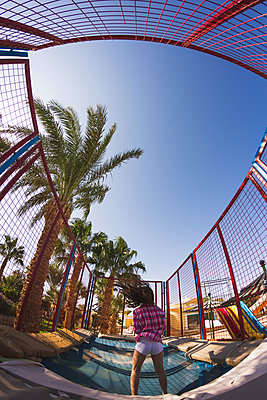 Rear view of girl jumping on a play park trampoline - p429m1504969 by Chuvashov Maxim