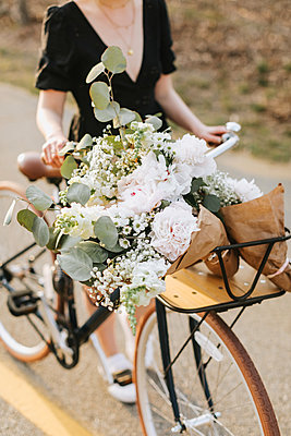 Young woman pushing bicycle with bunch of flowers on rural road, neck down, Menemsha, Martha's Vineyard, Massachusetts, USA - p924m2058142 by Lena Mirisola