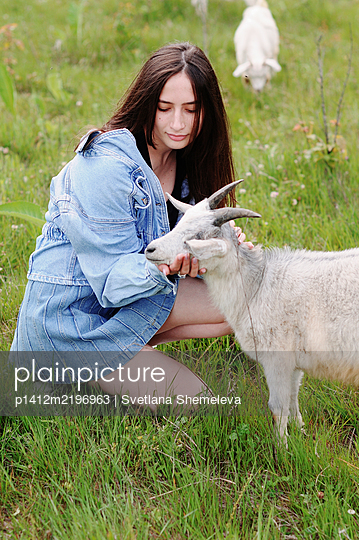 Woman with goat on a meadow, portrait - p1412m2196963 by Svetlana Shemeleva