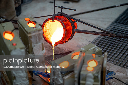 Container pouring melted bronze in workshop - p300m2286926 by Oscar Carrascosa Martinez