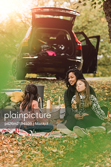 Mother and daughters enjoying picnic in autumn - p426m2194939 by Maskot