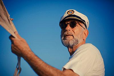 Croatia, Senior man with captain's hat steering sailboat - p1026m762715f by Romulic-Stojcic
