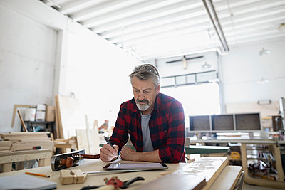 Male carpenter sketching with digital tablet stylus at workbench in workshop - p1192m1490208 by Hero Images