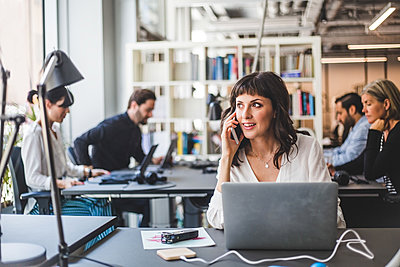 Businesswoman looking away while talking on mobile phone at desk in creative office - p426m2033976 by Maskot