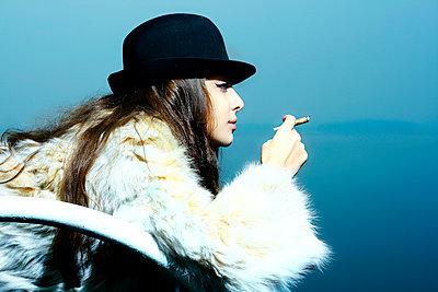 Portrait of glamorous woman wearing fur coat smoking cigarette - p555m1490952 by Aliyev Alexei Sergeevich