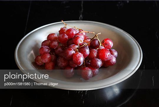 Wet red grapes on plate - p300m1581580 von Thomas Jäger