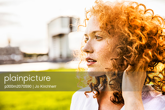 Germany, Cologne, portrait of freckled young woman with curly red hair - p300m2070590 by Jo Kirchherr