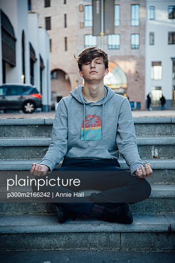 Teenager sitting on steps meditating in the city - p300m2166242 by Annie Hall
