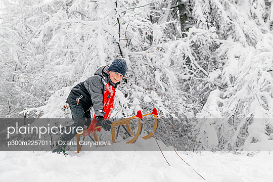 Boy sledding while playing with wooden sled on snow in forest - p300m2257011 by Oxana Guryanova
