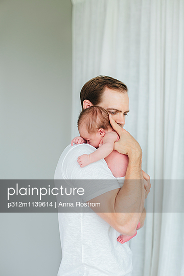 Father with newborn baby - p312m1139614 by Anna Rostrom