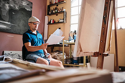 Man working as painter looking at reference image for new painting - p1166m2078296 by Cavan Images