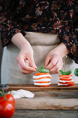 Woman's hands preparing Caprese Salad - p300m2012398 von Alberto Bogo