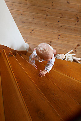 Baby girl climbing stairs - p352m2040145 by Christian Ferm