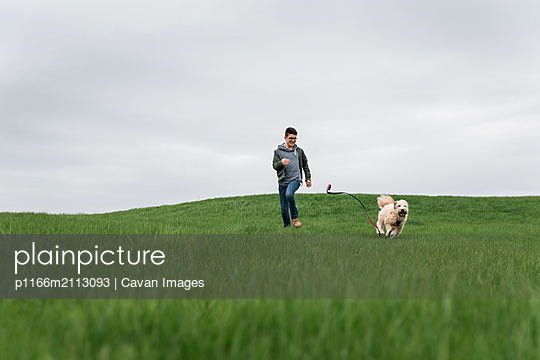 Teenage boy running across a grassy field with his dog on cloudy day. - p1166m2113093 by Cavan Images