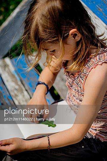 Mädchen bastelt in ihrem Heft - p1212m1146022 von harry + lidy