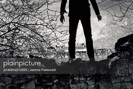 Person stands on stone wall, rear view - p1402m2212025 by Jerome Paressant